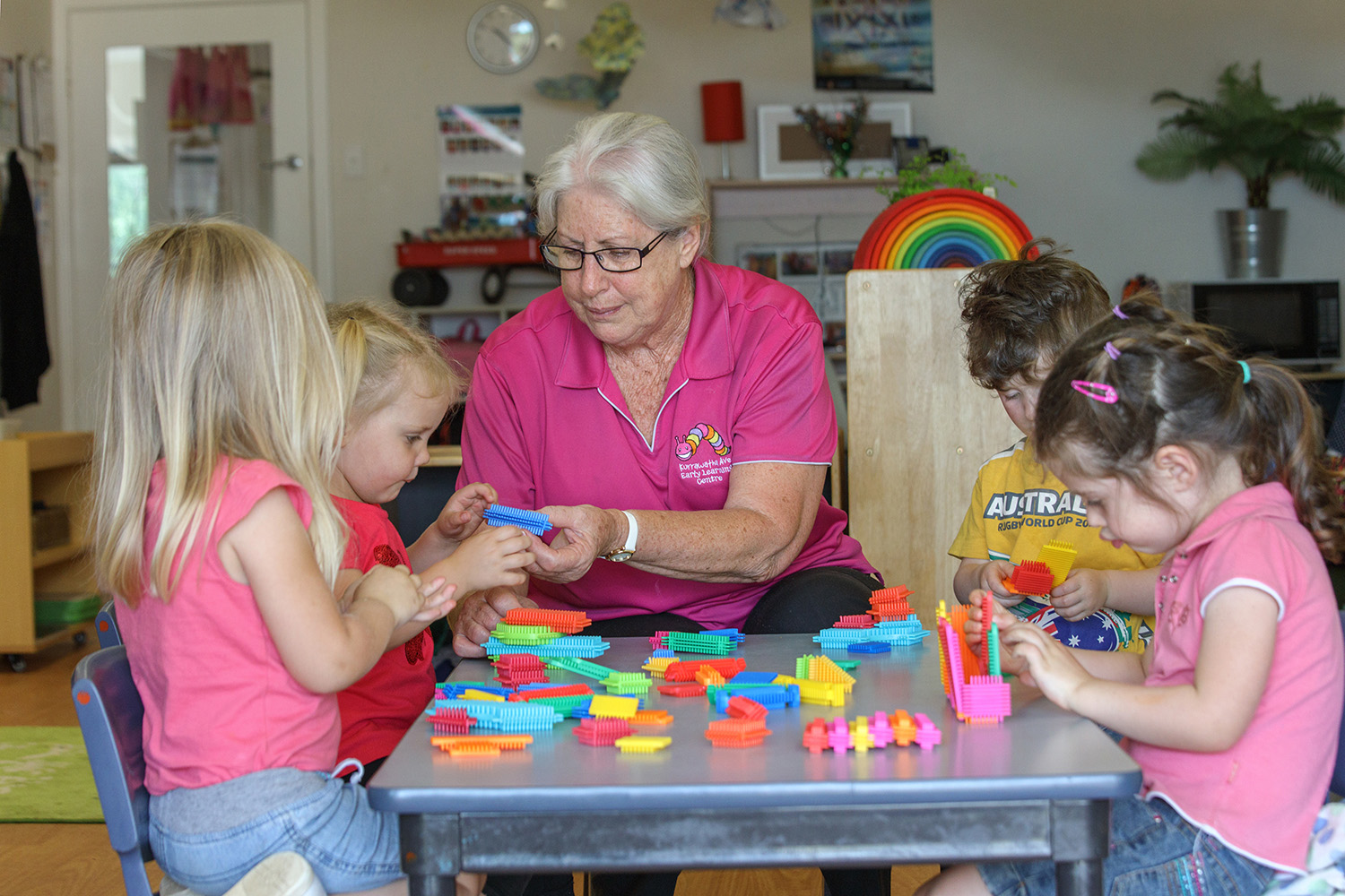 Child care educator playing puzzles with group of children at Kurrawatha ELC